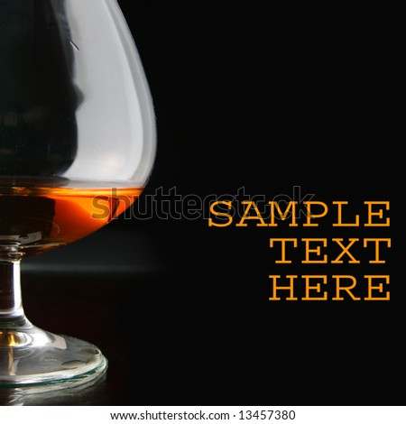 Glass of brandy over black background and space for your own text on right