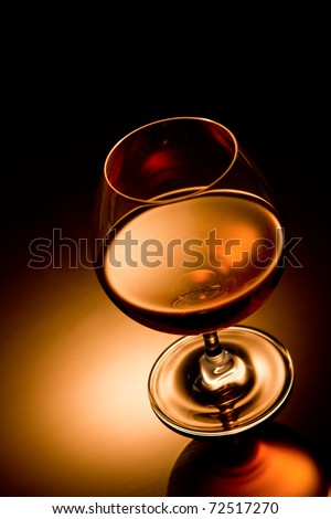 Glass of brandy over gold gradient background