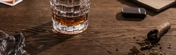 Glass of brandy with cigar, lighter and book on wooden table, panoramic shot,stock photo