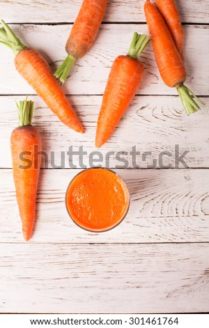 Glass of carrot juice and carrots on the white table