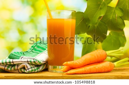 glass of carrot juice and fresh carrots on wooden table on green background