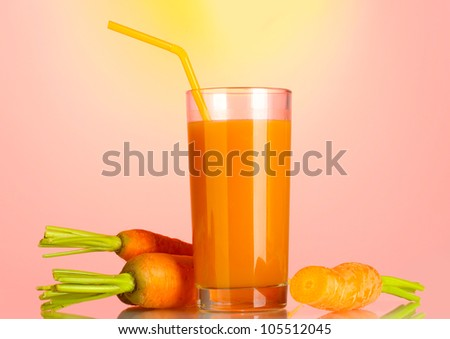 glass of carrot juice on pink-yellow background
