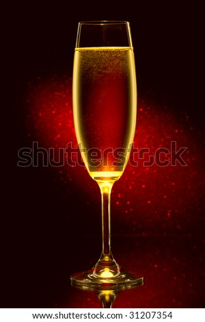 Glass of champagne  against a red background