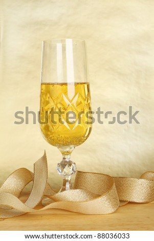 Glass of champagne and a gold ribbon against a gold background