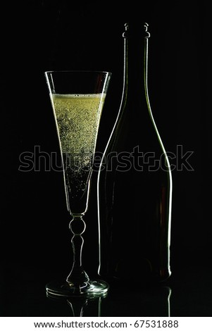 Glass of champagne and  bottle. Black background.