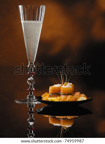 Glass of Champagne and Salmon Rolls With Reflection on Abstract Background