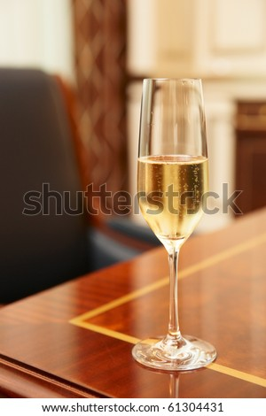 Glass of champagne on table in conference room