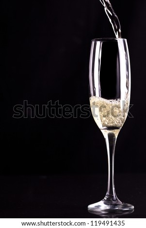 Glass of champaigne being filled against black background