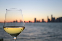 Glass of Chardonnay White Wine Overlooking the City of Miami Skyline Blurred After Dusk at Twilight in Key Biscayne, Florida