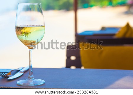 glass of chilled white wine on table near the beach #233284381