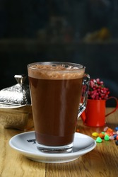 Glass of chocolate coffee with froth on table