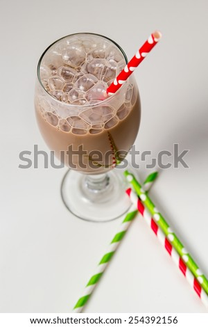 Glass of chocolate milk with bubbles and paper straws