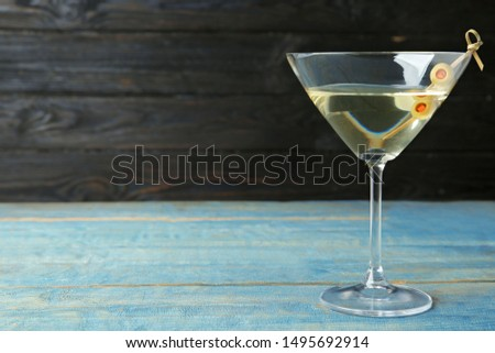 Glass of Classic Dry Martini with olives on light blue wooden table against dark background. Space for text #1495692914