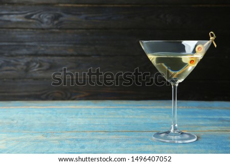 Glass of Classic Dry Martini with olives on light blue wooden table against dark background. Space for text #1496407052