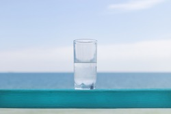glass of clean cool water against the background of the sea