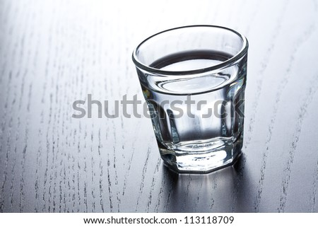 glass of clear alcohol on wooden table