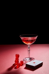 glass of cocktail near deck of cards and dice on red surface isolated on black