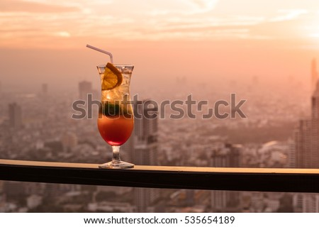 Glass of Cocktail Punch on Balcony with Sunset City View in the Background #535654189