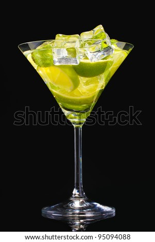 glass of cocktail with lime and mint on black background
