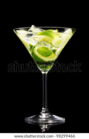 glass of cocktail with lime and mint on black background - stock photo