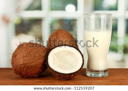 glass of coconut milk and coconuts on wooden table close-up