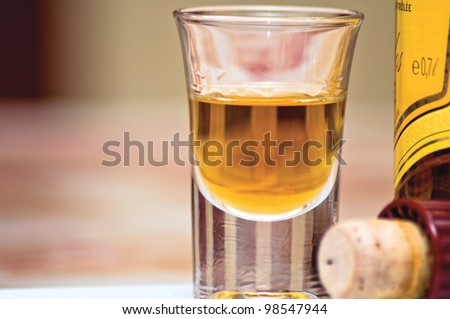 Glass of cognac. A glass of spirits, bottle and cork on the table