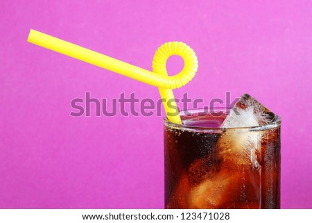 Glass of Cola with a yellow straw, cropped very close, on a purple background
