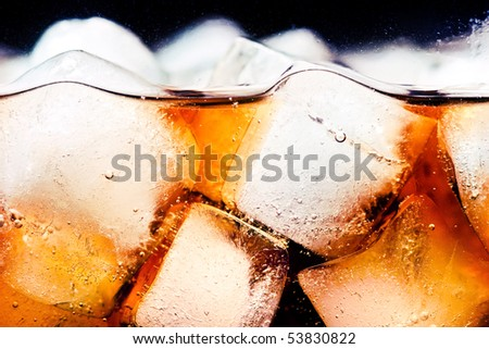 Glass of cola with ice cubes closeup