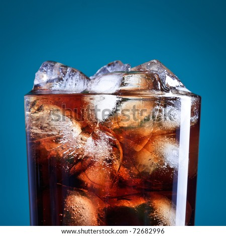glass of cola with ice on blue background
