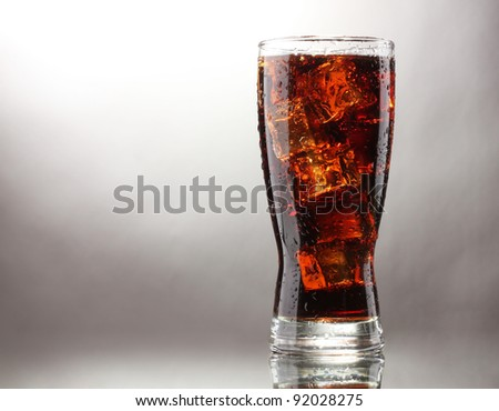 Glass of cola with ice on grey background