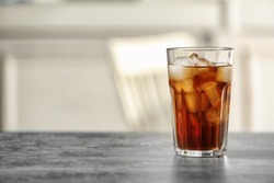 Glass of cola with ice on table against blurred background, space for text