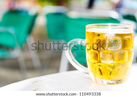 Glass of cold beer on table of street cafe