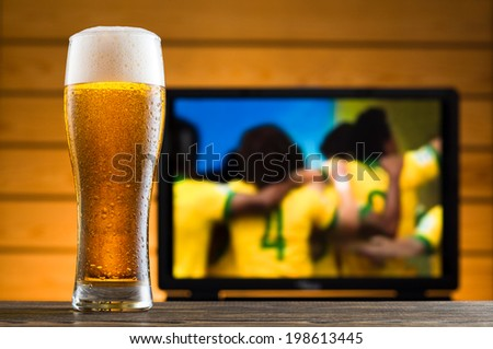 Glass of cold beer on the table, football match in background