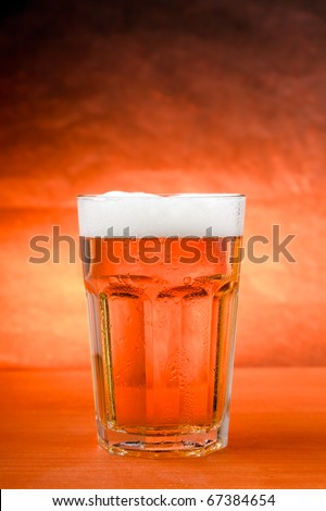 Glass of cold beer on wooden table with warm brown background