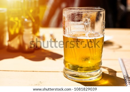 glass of cold beer outside on a table #1081829039