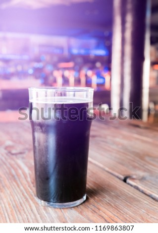 Glass of cold craft stout beer on the old table in old fashioned pub. #1169863807
