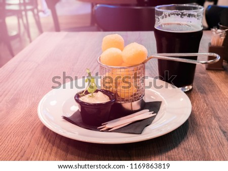 Glass of cold craft stout beer on the old table in old fashioned pub with cheese snacks #1169863819