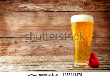 Glass of cold light beer with heart on a wood background for Valentine\'s day. toning. selective focus
