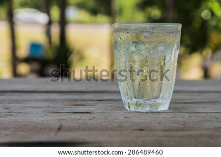 Glass of cold water, put the right on a wooden table. Focus on water drops on the glass with drops of water on the table.