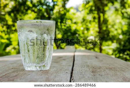 Glass of cold water shooting range Place the left side on a wooden table Focus on water drops on glass.