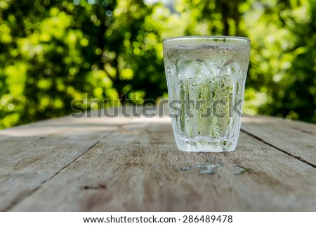 Glass of cold water shooting range Place the right side on a wooden table Focus on water drops on glass.