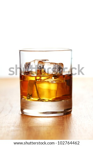 Glass of cold whiskey on wooden surface