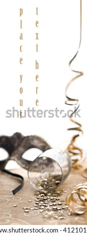 glass of confetti with mask and serpentine