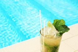 Glass of delicious mojito near swimming pool, space for text. Refreshing drink