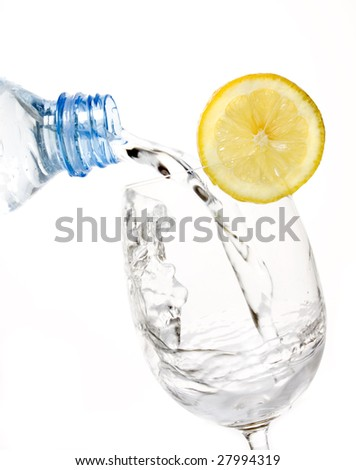 Glass of drinking water with lemon slice isolated on white - stock photo