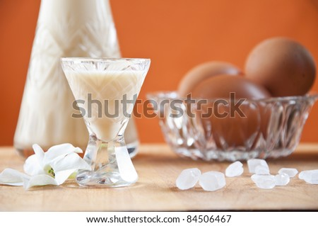 glass of eggnog with carafe and eggs