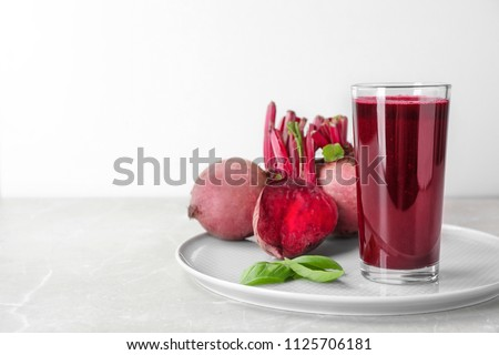 Glass of fresh beet juice, basil and vegetable on table