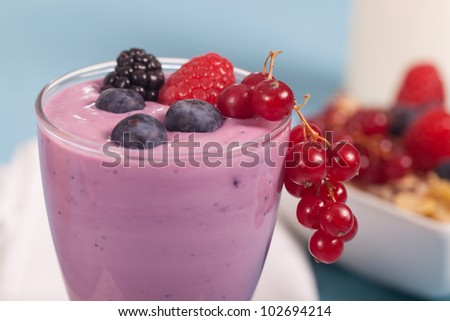 Glass of fresh delicious yogurt with berry fruits