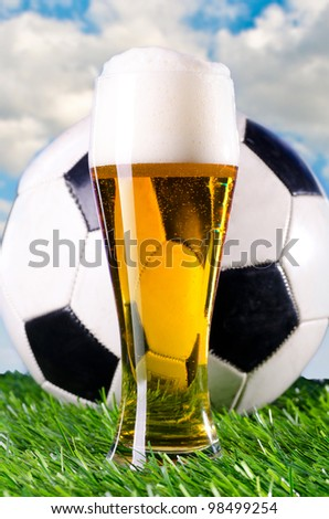 glass of fresh lager beer and ball against cloudy skies