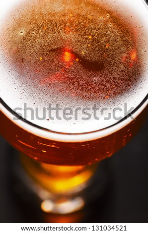 glass of fresh lager beer on black table